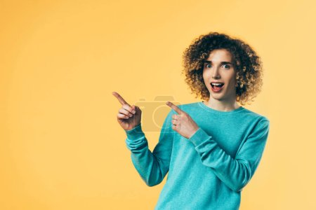 Photo pour Curly teenager with open mouth pointing with fingers aside isolated on yellow - image libre de droit