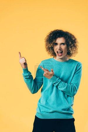 Photo pour Excité adolescent bouclé avec bouche ouverte pointant avec les doigts de côté isolé sur jaune - image libre de droit