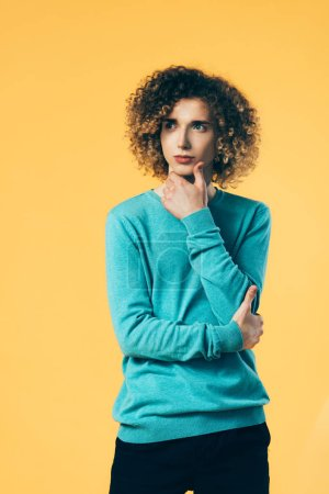 Photo pour Pensive curly adolescent regardant loin isolé sur jaune - image libre de droit