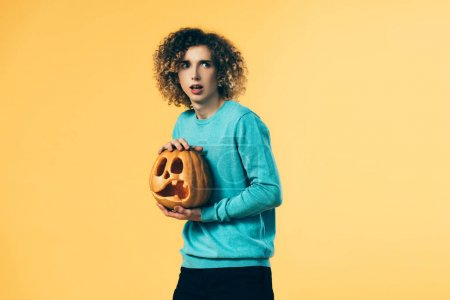 Photo for Scared curly teenager holding pumpkin isolated on yellow - Royalty Free Image