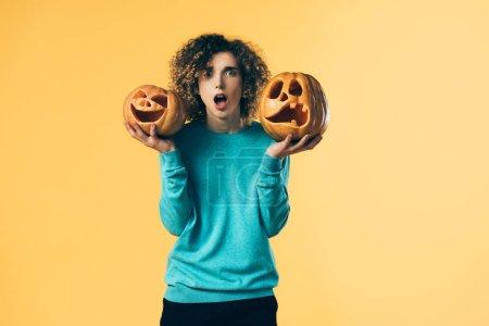 Photo pour Choqué adolescent bouclé tenant citrouilles Halloween isolé sur jaune - image libre de droit
