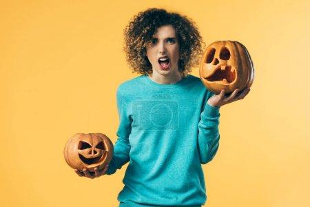 Photo pour Adolescent frisé effrayé tenant citrouilles Halloween et hurlant isolé sur jaune - image libre de droit