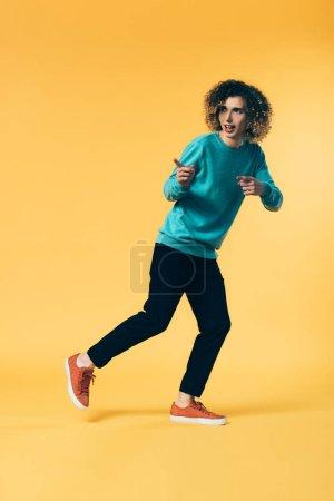 Photo pour Vue pleine longueur d'un adolescent courbé courant et pointant avec les doigts sur le jaune - image libre de droit
