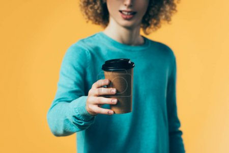 Photo pour Foyer sélectif de l'adolescent bouclé tenant café dans une tasse en papier isolé sur jaune - image libre de droit