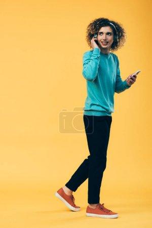 Photo pour Adolescent bouclé souriant tenant smartphone et écouter de la musique dans les écouteurs tout en marchant sur jaune - image libre de droit