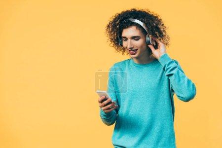Photo pour Un adolescent souriant utilisant un smartphone et écoutant de la musique dans un casque isolé en jaune - image libre de droit
