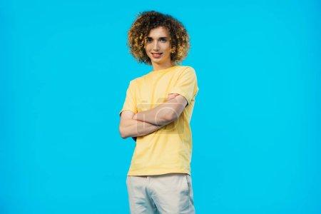 Photo pour Une adolescente souriante aux bras croisés isolée sur fond bleu - image libre de droit