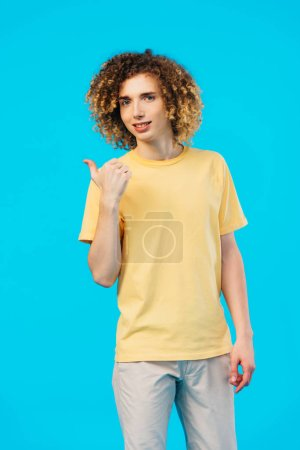 Photo pour Souriant bouclé adolescent montrant pouce vers le haut isolé sur bleu - image libre de droit