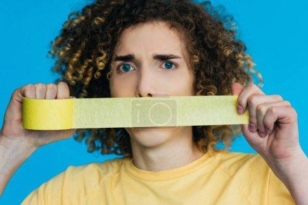 Photo pour Inquiet adolescent bouclé tenant du ruban adhésif près de la bouche isolé sur bleu - image libre de droit