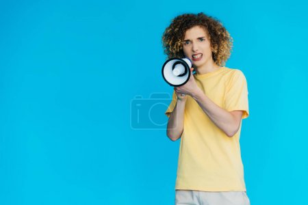 Photo pour Angry curly teenager screaming in loudspeaker isolated on blue - image libre de droit