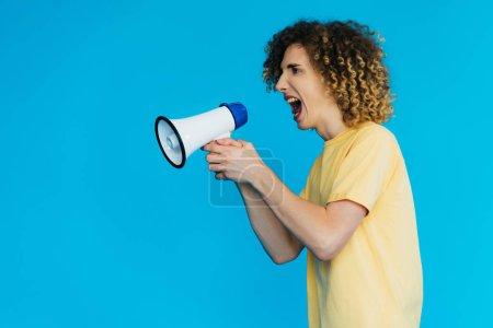 Photo pour Vue latérale d'un adolescent en colère criant dans un haut-parleur isolé sur fond bleu - image libre de droit