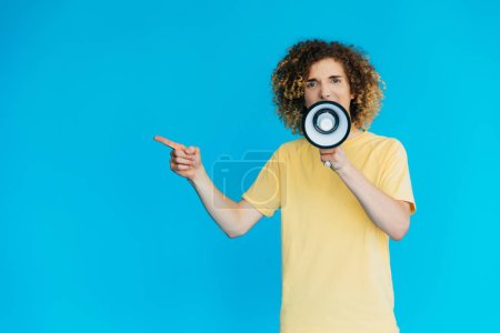 Photo pour Angry curly teenager screaming in loudspeaker and pointing with finger isolated on blue - image libre de droit