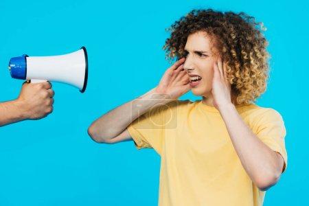 Photo pour Vue recadrée de l'homme tenant haut-parleur près de l'adolescent frisé couvrant les oreilles isolées sur bleu - image libre de droit