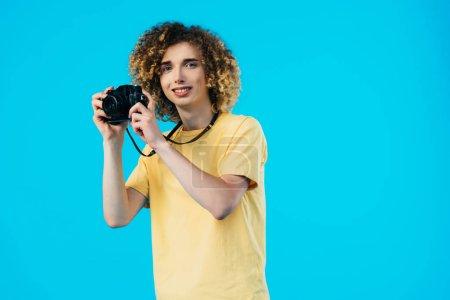 Photo pour Une adolescente souriante prend des photos sur une caméra isolée sur un film bleu - image libre de droit
