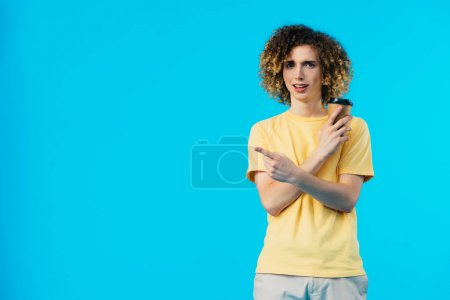 Photo for Curly teenager with coffee to go pointing with finger aside isolated on blue - Royalty Free Image