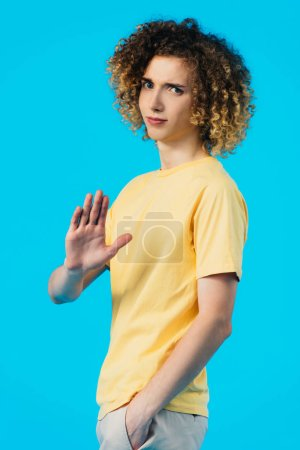 Photo pour Upset curly teenager with hand in pocket showing stop gesture isolated on blue - image libre de droit