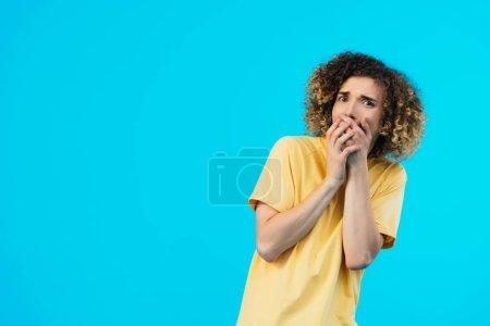 Photo pour Peur frisée adolescent couvrant la bouche avec les mains isolées sur bleu - image libre de droit