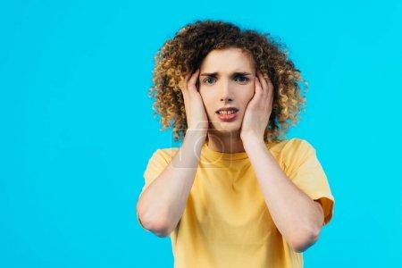 Photo pour Adolescent bouclé stressé couvrant les oreilles avec les mains isolées sur bleu - image libre de droit