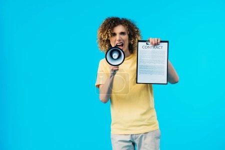 Photo pour Un adolescent furieux tenant un contrat et criant en mégaphone isolé en bleu - image libre de droit