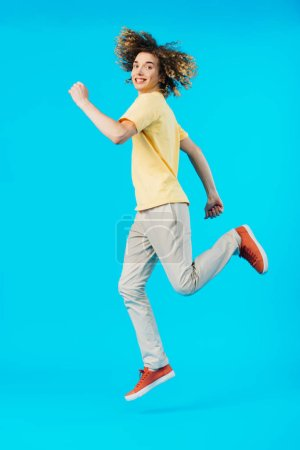 Photo for Happy curly teenager jumping isolated on blue - Royalty Free Image