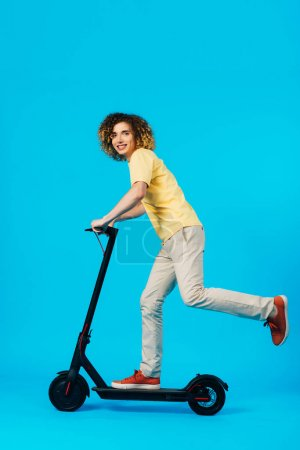 Photo pour Side view of happy curly teenager riding electric scooter on blue background - image libre de droit