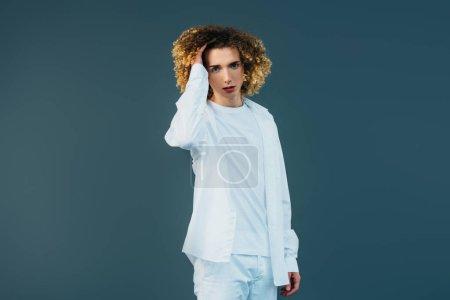 Photo pour Curly adolescent en complet costume blanc touchant les cheveux isolés sur le vert - image libre de droit
