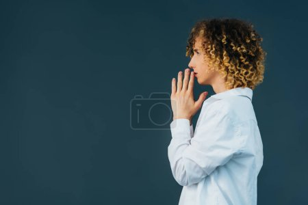 Photo pour Side view of curly teenager in total white outfit with praying hands isolated on green - image libre de droit