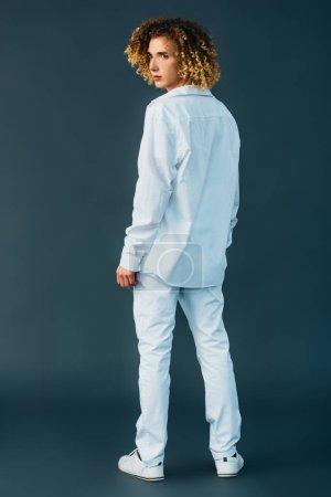 Photo pour Vue arrière de l'adolescent bouclé en tenue blanche totale isolé sur vert - image libre de droit