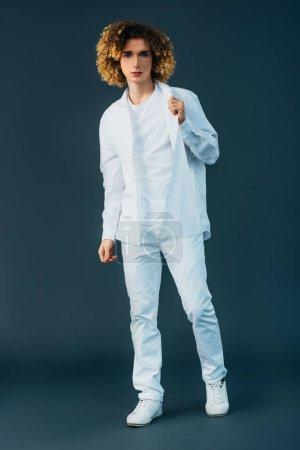 Photo pour Vue pleine longueur de l'adolescent bouclé en complet blanc posant isolé sur vert - image libre de droit