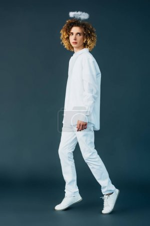 Photo pour Full length view of curly teenager in angel costume with halo above head on green - image libre de droit