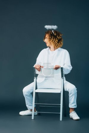 Photo pour Smiling curly teenager in angel costume with halo above head sitting on chair on green - image libre de droit