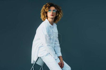 Photo pour Une adolescente élégante en tenue entièrement blanche et des lunettes qui ne regardent pas tout en étant assise sur une chaise isolée sur un fond vert - image libre de droit