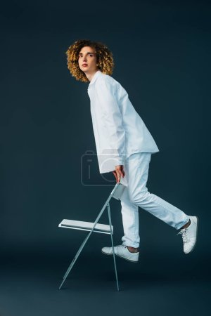 stylish curly teenager in total white outfit standing on chair on green