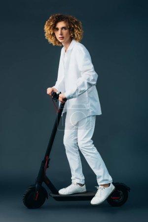 Photo pour Adolescent bouclé élégant en tenue blanche totale équitation scooter électrique sur vert - image libre de droit