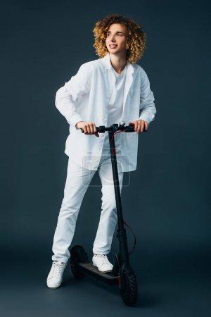 Photo pour Sourire élégant adolescent bouclé en tenue blanche totale équitation scooter électrique sur vert - image libre de droit