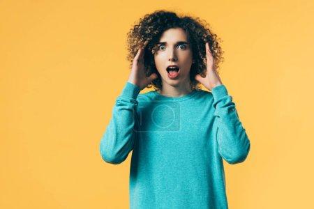 Photo pour Adolescent frisé effrayé avec bouche ouverte isolé sur jaune - image libre de droit