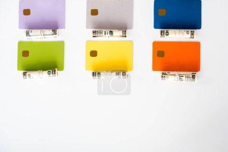 Photo pour Vue de dessus des modèles colorés de carte de crédit près des rouleaux de trésorerie avec des billets en dollars isolés sur blanc - image libre de droit