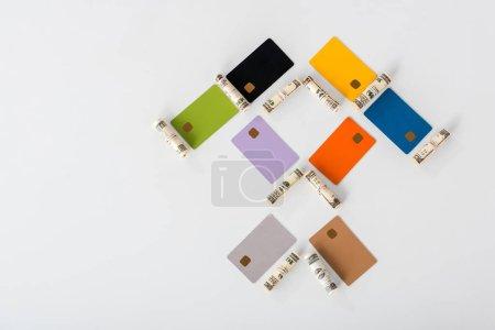 Photo pour Pose plate avec des modèles de cartes de crédit multicolores près de rouleaux de trésorerie sur blanc - image libre de droit