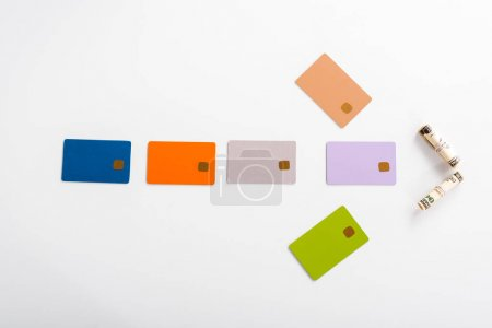 Photo for Top view of colorful credit card templates and cash rolls on white - Royalty Free Image