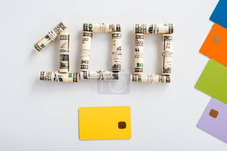 Photo for Top view of one hundred dollar banknotes in cash rolls near colorful credit card templates on white - Royalty Free Image