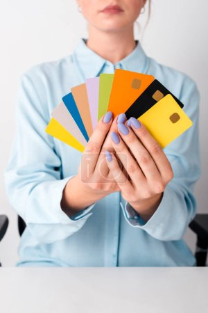 Photo for Cropped view of woman holding colorful credit card templates isolated on white - Royalty Free Image