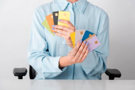 Photo for Cropped view of woman holding multicolored credit card templates in hands isolated on white - Royalty Free Image