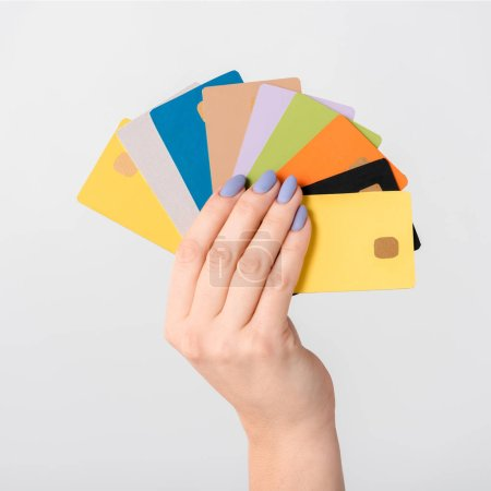 Photo pour Cropped view of woman holding colorful credit card templates in hand isolated on white - image libre de droit