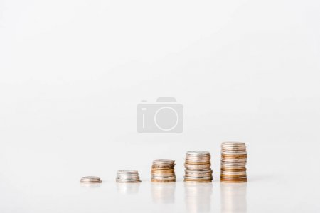 Photo pour Stacks of silver and golden coins on white - image libre de droit