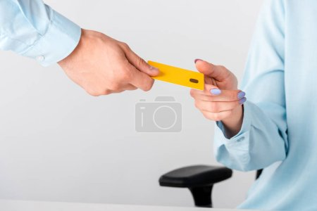 Photo for Cropped view of man giving yellow credit card template to woman isolated on white - Royalty Free Image