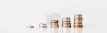 panoramic shot of stacks of silver and golden coins on white