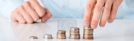 Photo pour Panoramic shot of man touching stack of coins isolated on white - image libre de droit