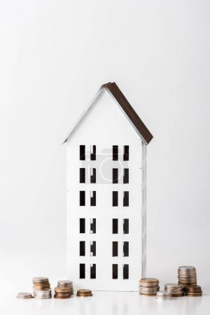 Photo pour Carton maison près des piles avec des pièces sur blanc - image libre de droit