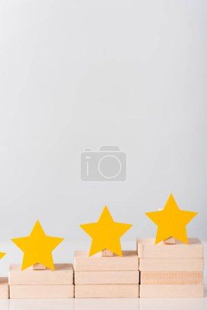 Photo pour Étoiles jaunes sur des blocs de bois comme concept de carrière isolé sur blanc - image libre de droit