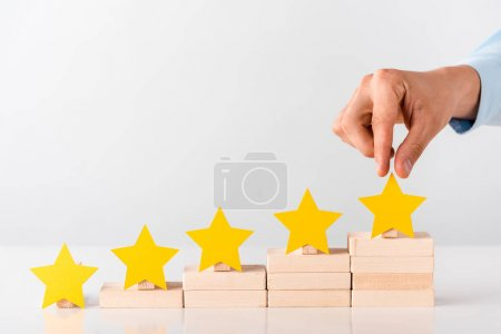 cropped view of man touching yellow star on white